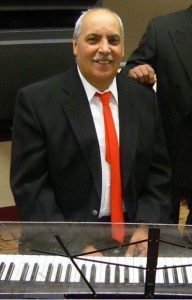 Joe Velez sitting behind a keyboard wearing a black suit and red tie, smiling