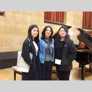 Marineh Kirakosyan posing with her students in front of a piano in Robyn Newhouse Hall