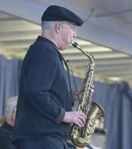 Ed Mari standing and playing saxophone in a concert