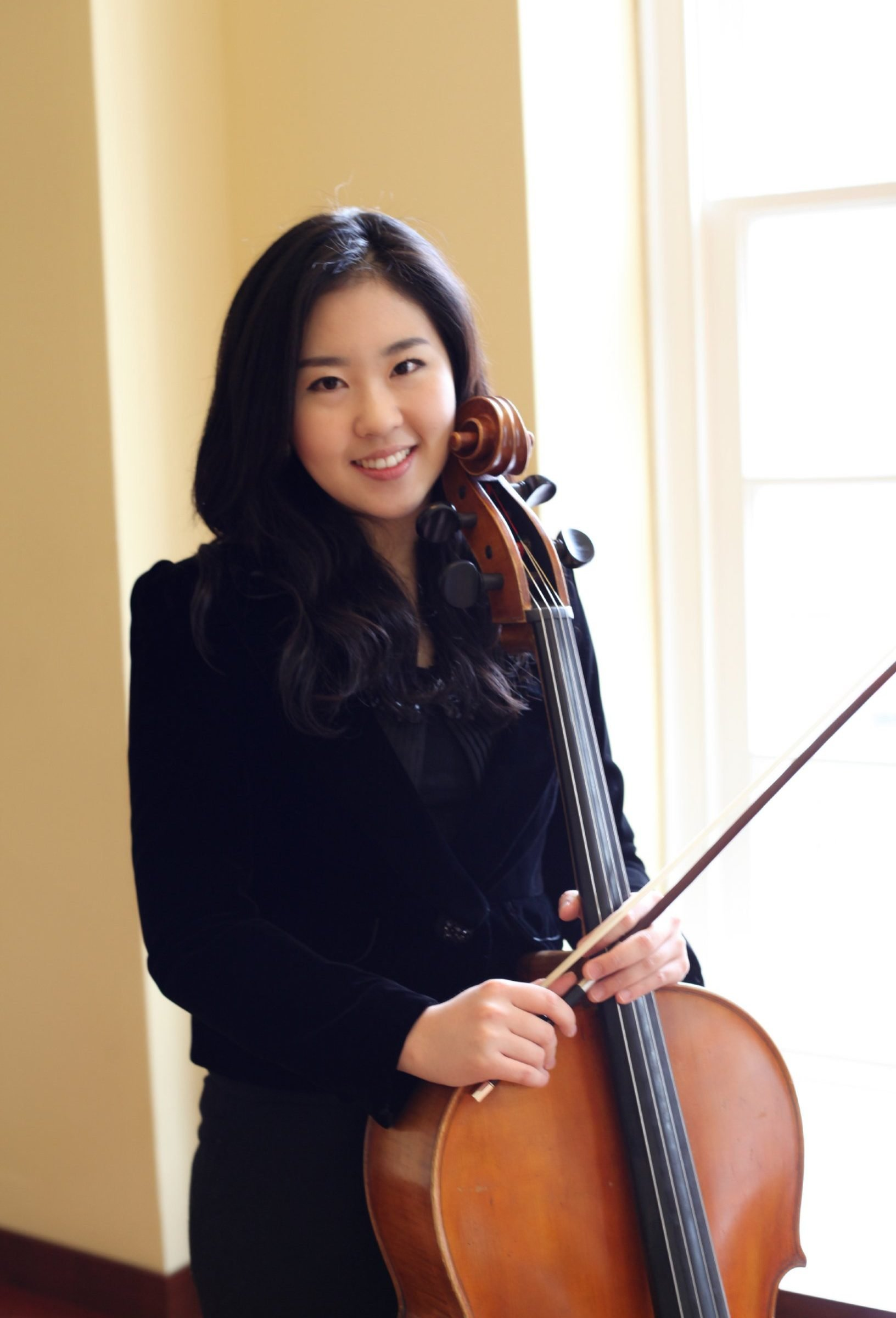 Yoonhee Ko posing and smiling with her cello in front of sunny window
