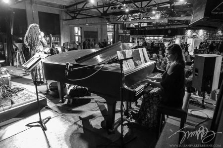 black and white photo of mara playing piano to accompany performers
