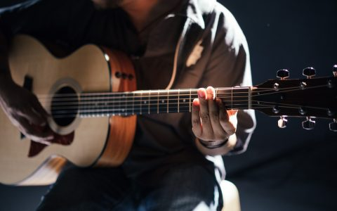 the torso of someone playing an acoustic guitar