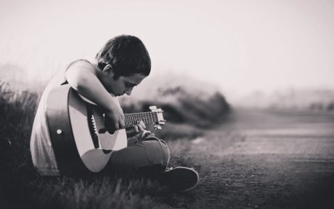 profile shot of a person playing guitar outdoors in the grass, black and white