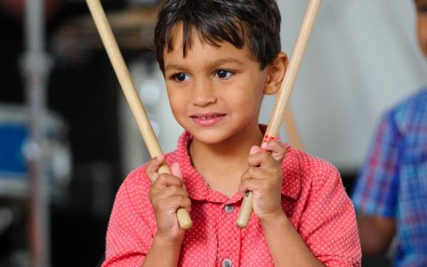 child holding up drum sticks and smiling