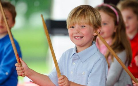 Child smiling with drum sticks and other children in the blurred background