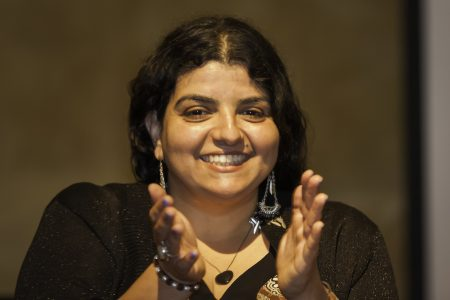 Eleni Yalanis clapping and smiling, showing from the shoulders and above, with a blurred background