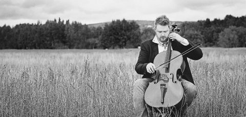 Karl Knapp playing the cello in a field, photo in black and white