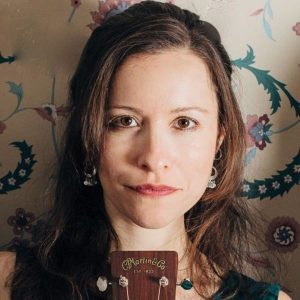 Headshot of Liz Simmons, against flower-patterned wall, showing shoulders and up with top of a guitar on the bottom of picture