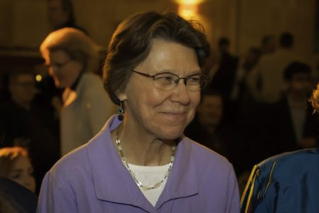 Headshot of Mary Ellen Miller smiling and looking to the side in a group of people, wearing a purple blouse, blurred background