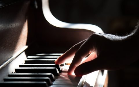 close up of an adult hand playing one end of a piano keyboard