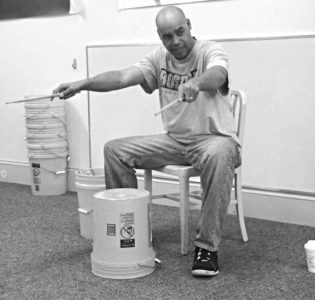 Rick Marshall teaching a bucket drum lesson with his arms stretched out in front holding drum sticks