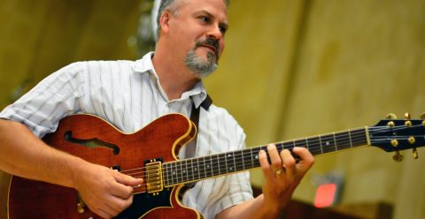 Scott Sasanecki playing the electric guitar in Robyn Newhouse Hall