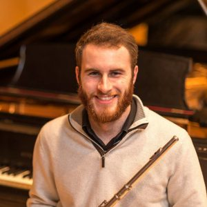 Headshot of Zach Robarge sitting at a piano with his flute smiling