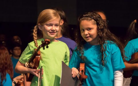 Close up of two Sonido string students holding their violins and smiling on stage at MLK performance