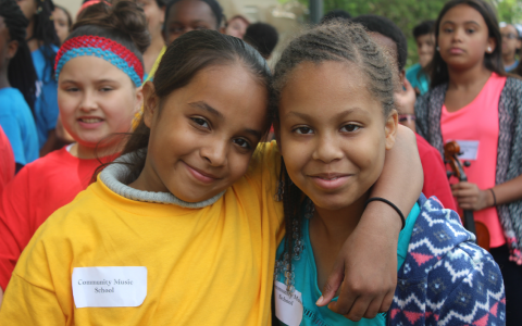 Two students posing, one with their arm around the other smiling, other students blurred in the background