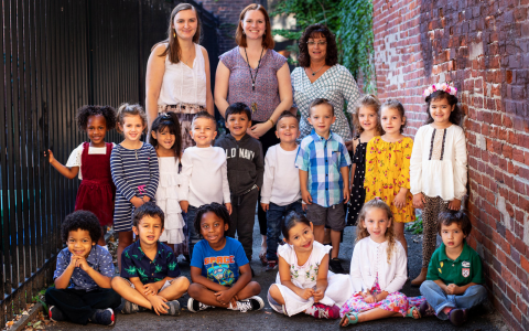 Class photo of a prelude preschool class, students in front and teachers behind