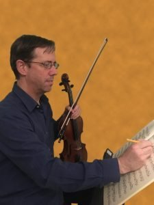 greg holding violin and bow with sheet music in front of him, writing on sheet music with a pencil