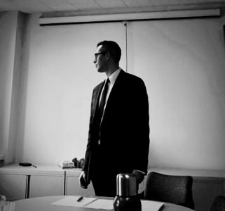 black and white photo of matthew wearing a suit and tie, standing and looking to his right in the front of a classroom