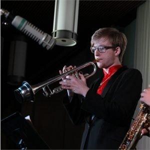 Justin Esiason playing trumpet in a recording studio