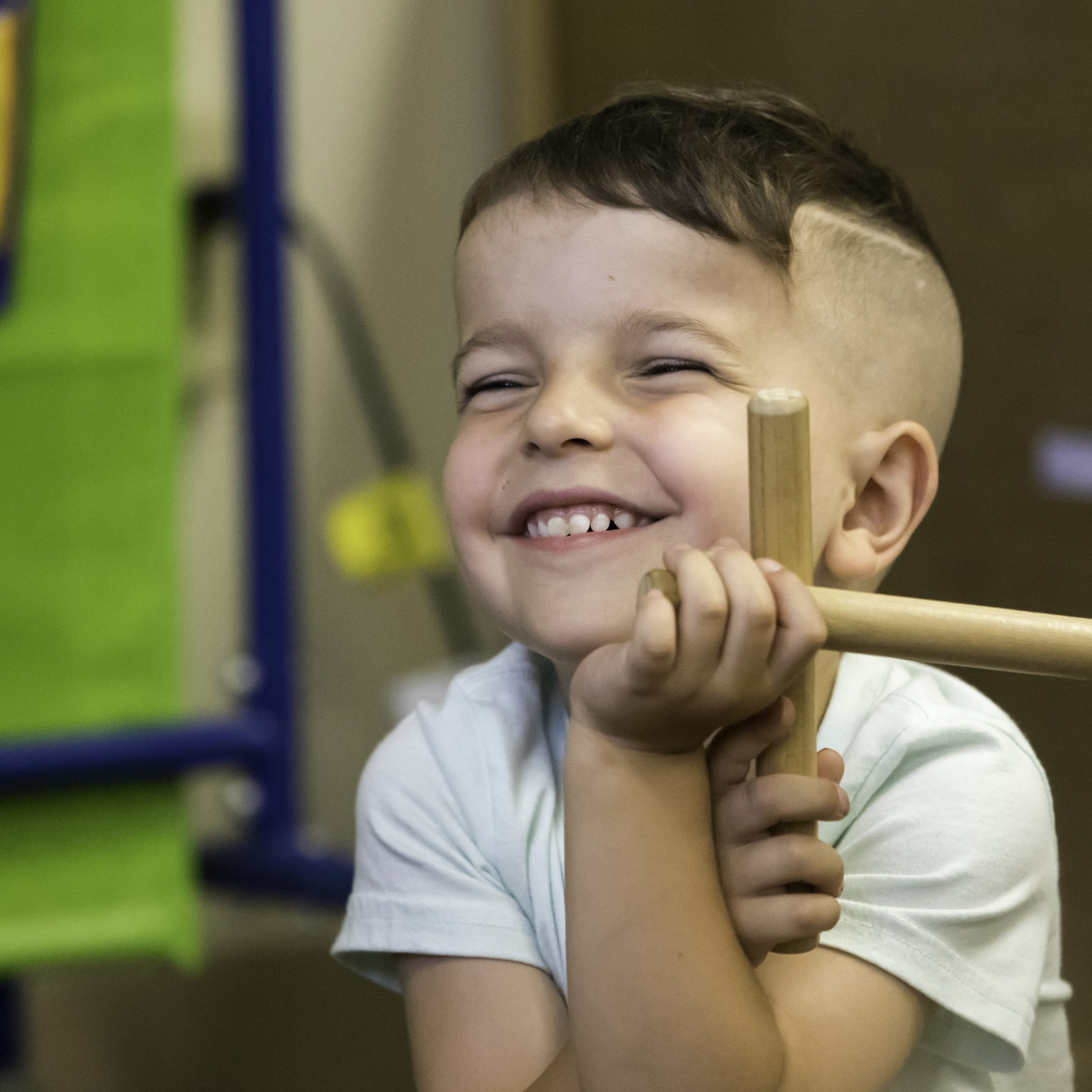 Prelude student smiling, holding wooden claves/rhythm sticks