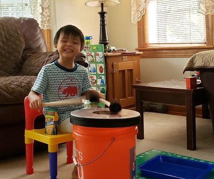 prelude student playing bucket drum in living room