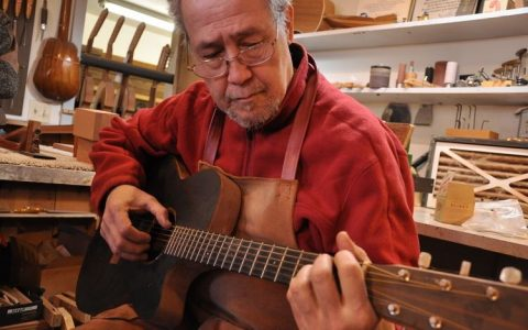 William Cumpiano playing a guitar in his workshop