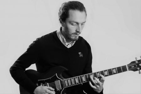 Chris playing electric guitar, looking calmly down at the instrument