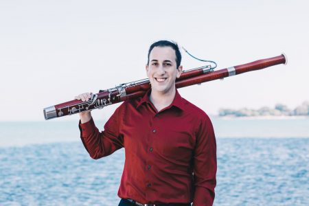 Vinny holding his bassoon over his shoulder, standing in front of a body of water