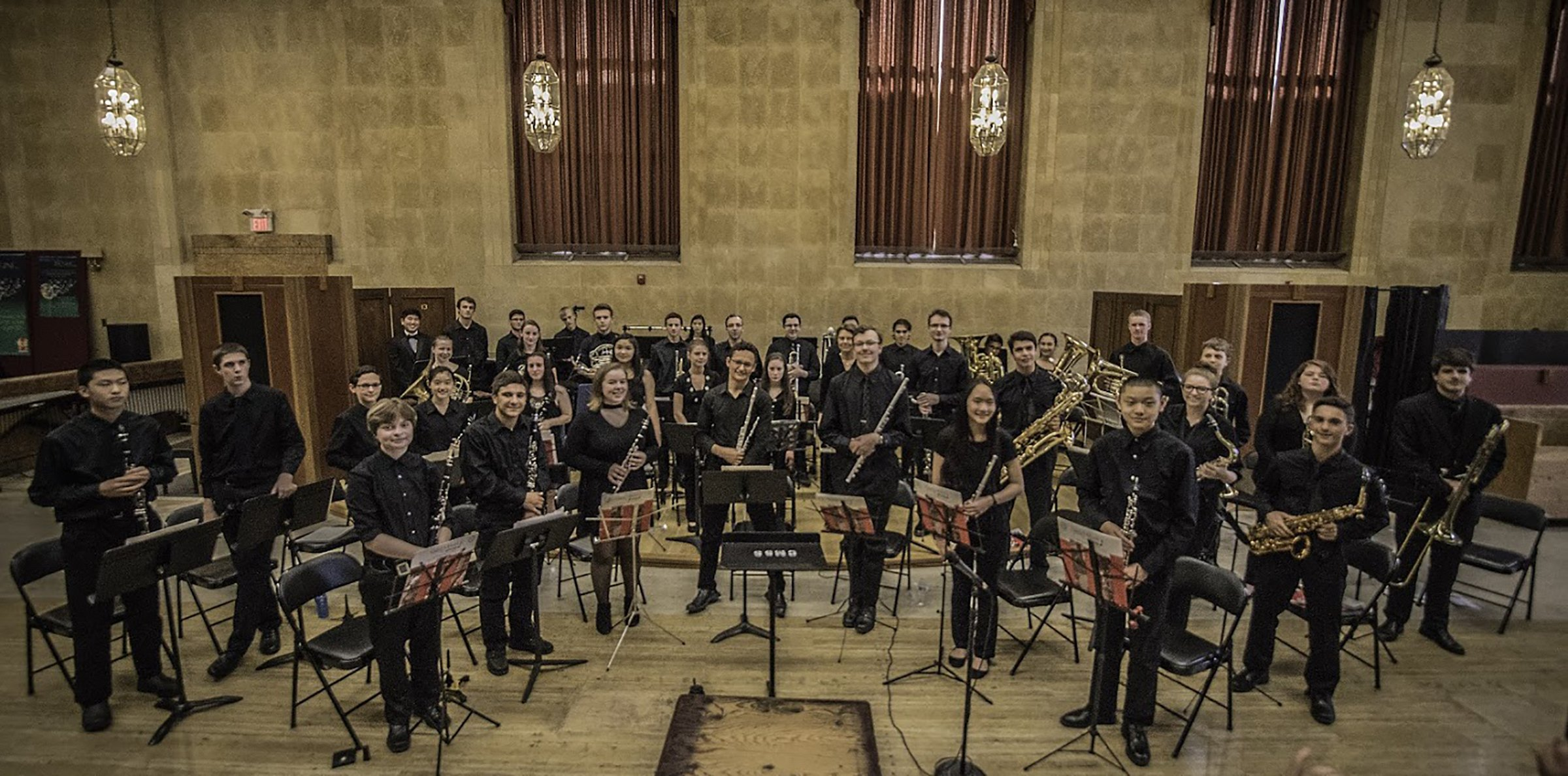 Youth Wind Ensemble students standing with their instruments after performing
